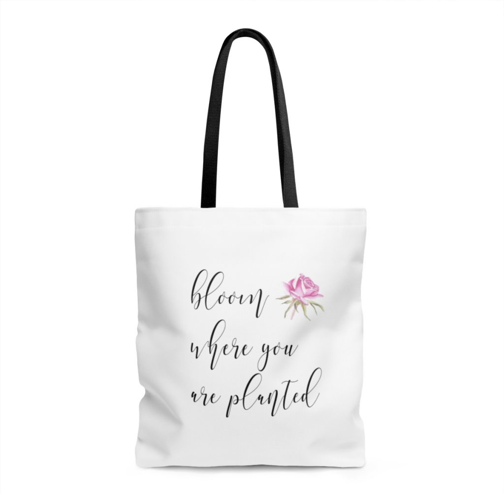 "white tote bag with black handle with quote,""bloom where you are planted"" and a watercolour rose"