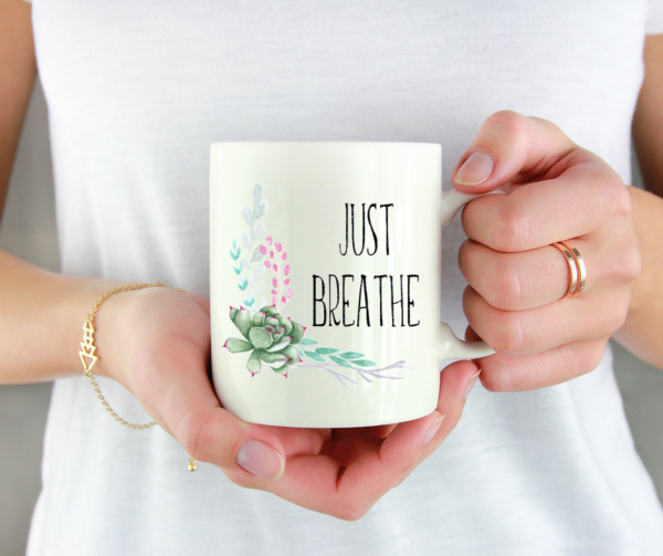 woman-holding-just-breathe-floral-mug