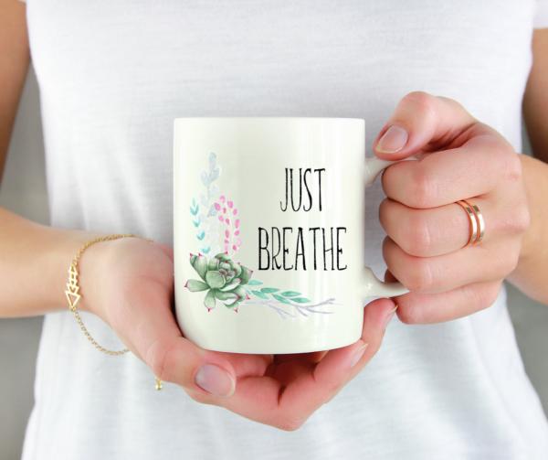 woman-holding-just-breathe-floral-mug